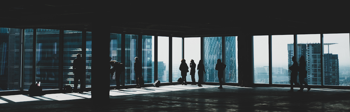 silhouette of business men and women overlooking high rise building